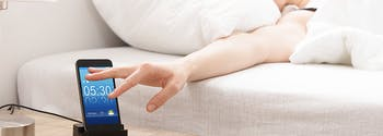 image of woman reaching for alarm clock in bed