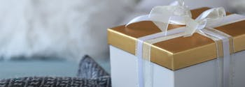 gift box from wedding registry on top of bed with cozy sheets and pillows
