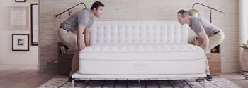 mattress deliverypeople setting up new mattress