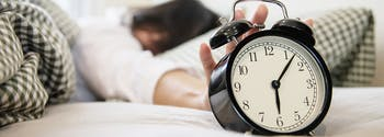 image of woman reaching for alarm clock - how much sleep do you need
