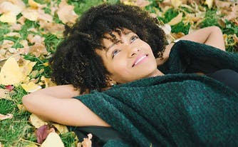 image of woman lying in grass in fall - change of seasons and sleep