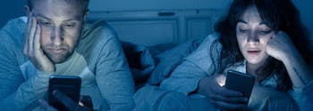 couple in bed on phones in the middle of the night