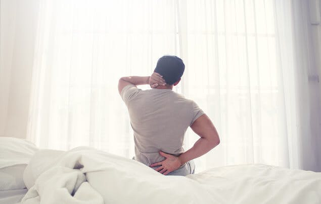 health effects of old mattress - person holding back in pain