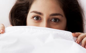 how to deal with acid reflux at night - image of woman under covers in bed
