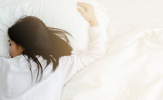 image of woman sleeping on stomach - best memory foam mattress for stomach sleepers