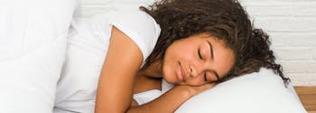 best combination sleeper pillow - image of person lying in bed