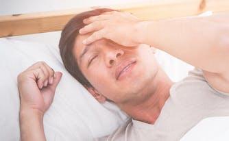 signs you need new mattress - person uncomfortable in bed