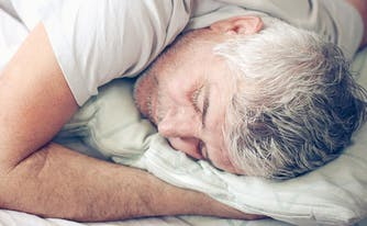 best latex mattress for stomach sleepers - image of man lying on stomach