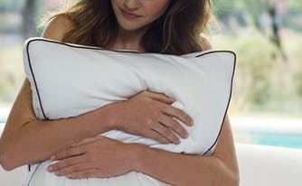 how to pick the best pillow - image of woman hugging pillow