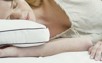 image of woman sleeping on side with pillow