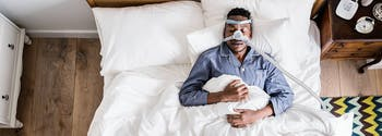 image of man with sleep apnea wearing CPAP machine