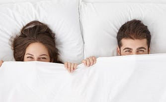 sleep habits of couples survey results - image of couple in bed