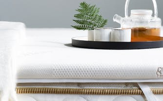 image of mattress topper with blanket and tea pot