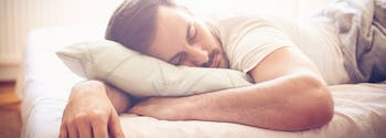 image of man with back pain sleeping