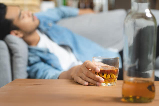 person holding whiskey glass and sleeping on couch
