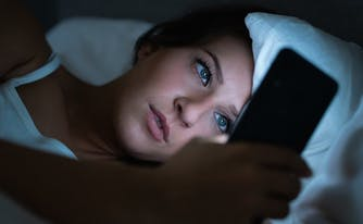 image of person on social media in bed