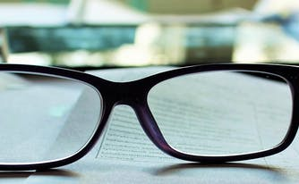 mattress fine print policies - image of glasses on book