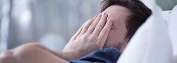 image of sleep-deprived man in bed