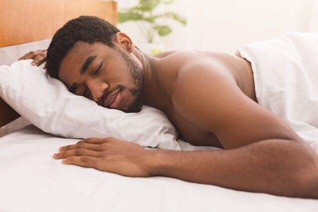 person sleeping on stomach, which can cause a stiff neck