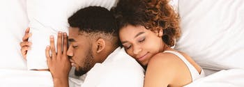 best sex pillow - image of couple cuddling in bed