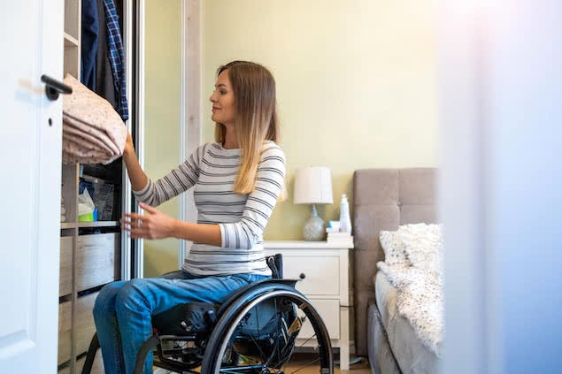person in wheelchair putting sheets away in closet