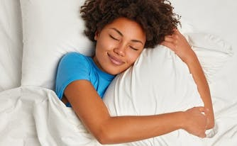 image of person hugging pillow in bed