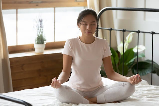 image of person meditating on bed to relieve headache-causing stress