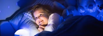 image of little kid in bed with night light