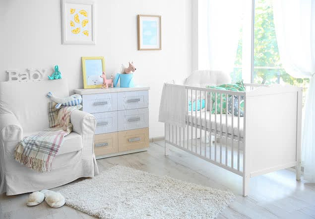 baby nursery with crib, dresser, and chair