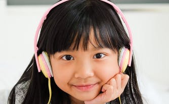 image of child listening to music in bed