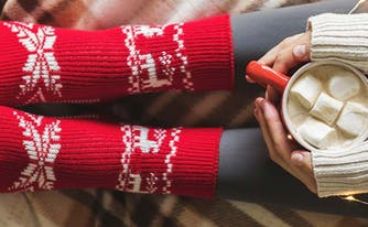 image of woman's feet in red socks holding hot chocolate in cozy winter bedroom