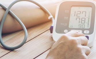 person using blood pressure monitor