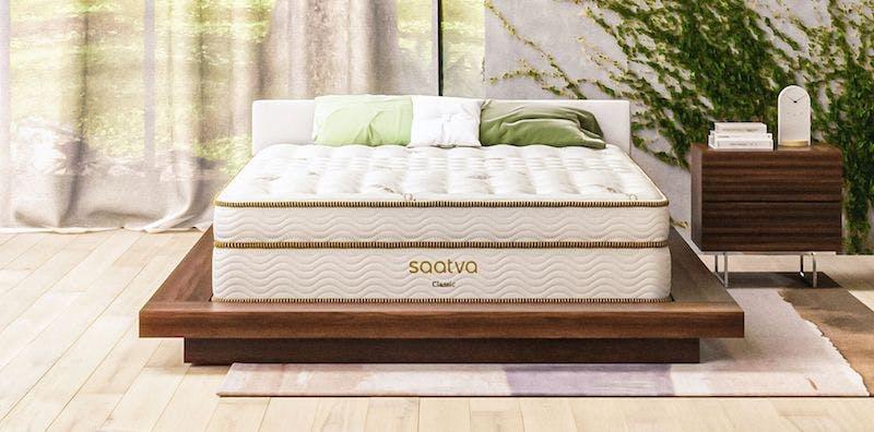 saatva classic innerspring mattress on wood platform next to nightstand table