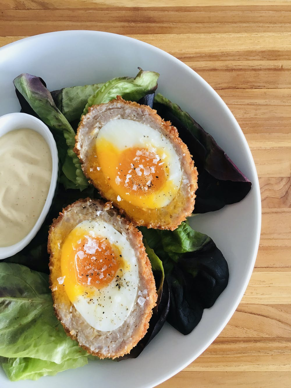 scotch eggs on a plate with salad and mustard sauce
