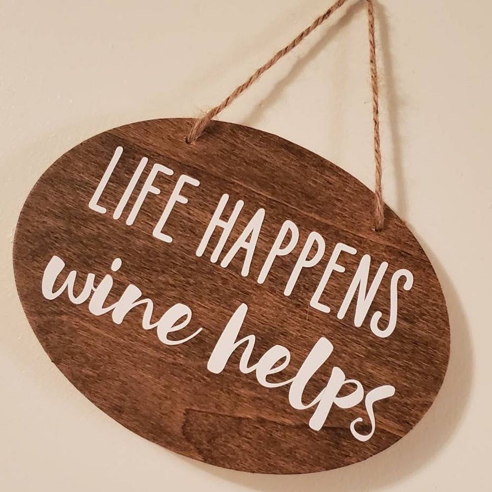 """wooden sign with the words """"life happens wine helps"""" on it"""