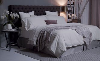 bedroom with a saatva mattress that has pillows and a gray throw blanket on top if it
