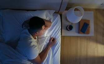 person looking at smart home device from bed