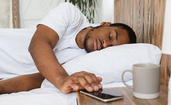 person oversleeping in bed