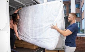 people storing a mattress in a van