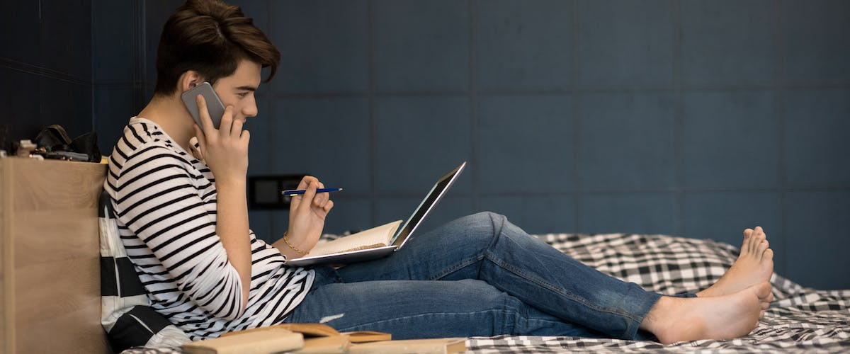 teenager talking on phone with computer and notebook open in bed