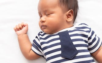 baby sleeping on top of bed with arm raised