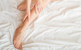 how to sleep better with restless legs syndrome - image of legs in bed