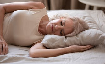 person sleeping on side on innerspring mattress