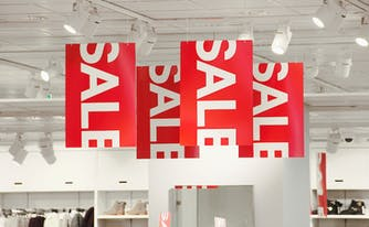 image of red sale signs - best time to buy a mattress