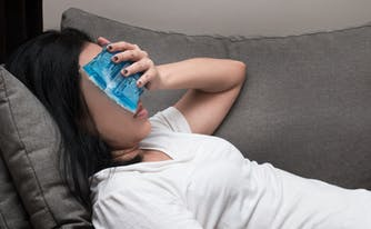 person with ice pack over face to cool down from night sweats