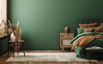 bedroom with green walls - bed with green and brown sheets on it with a nightstand next to it with wood vase on top