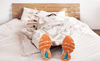 athlete lying on top of mattress with sneakers on