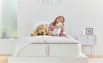 toddler sitting on top of big kid bed with stuffed animals