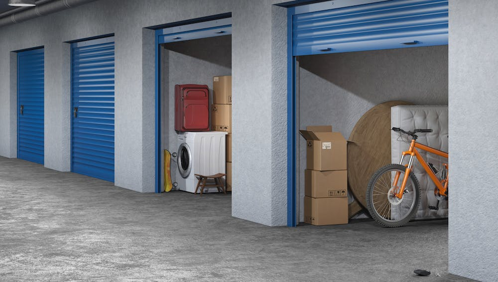 storage unit with a mattress, bicycle, table, and boxes in it