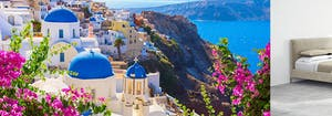 white buildings with blue domes on Santorini coastline, next to Saatva's Santorini platform bed frame